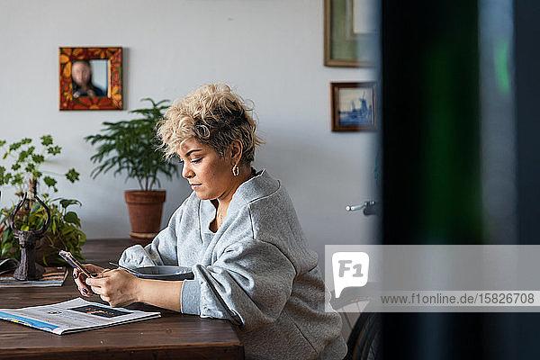 Mittlere erwachsene Frau  die ein Smartphone benutzt  während sie mit einer Schüssel am Tisch im Wohnzimmer sitzt