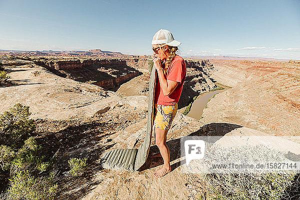 weiblicher Camper sprengt Schlafkissen auf einem Campingplatz oberhalb des Grand Canyon in die Luft