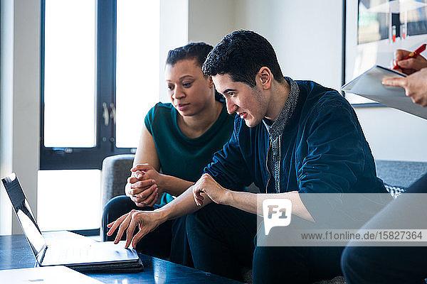 Kollegin betrachtet Geschäftsmann mit Laptop auf Tisch im Büro