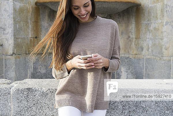 Lächelnde Frau benutzt ihr Telefon  während sie sich an einen Brunnen in Boadilla lehnt