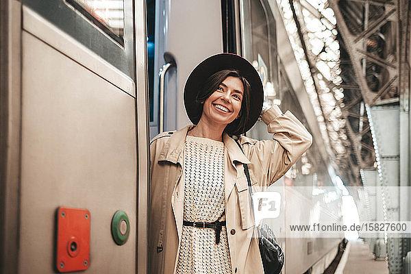 Junge stilvolle Reisende hängt und lächelt im Zug