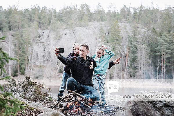 Vater nimmt sich mit seinen Kindern am Lagerfeuer sitzend mit