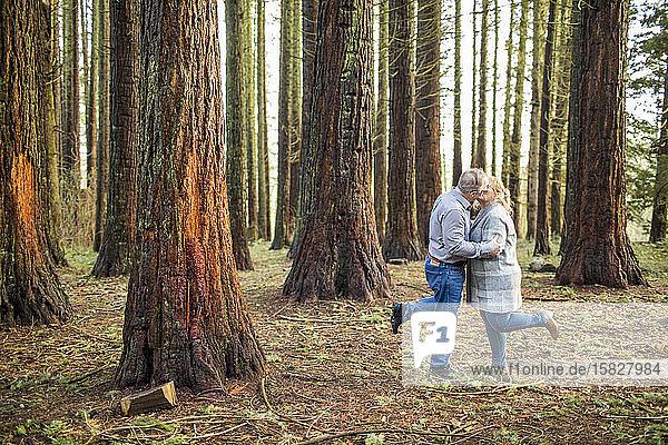 Romantisches Ehepaar im Ruhestand  das sich im Wald küsst.