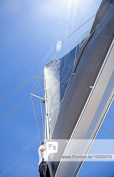 A sailor on the foredeck of a catamaran checking on the rigging durin
