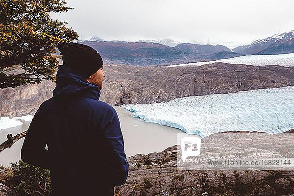 Stehender Mann mit Blick auf See und Gletscher