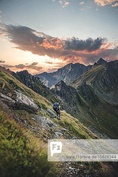 Mann auf Wanderweg mit Aussicht im Hintergrund bei Sonnenuntergang