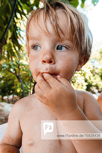 Little boy eating a berry