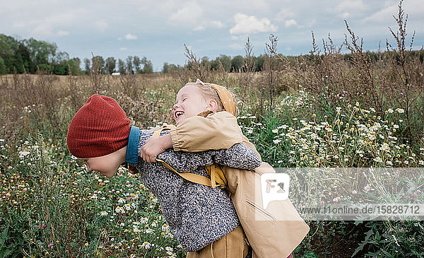 brother and sister hugging and laughing whilst playing outside