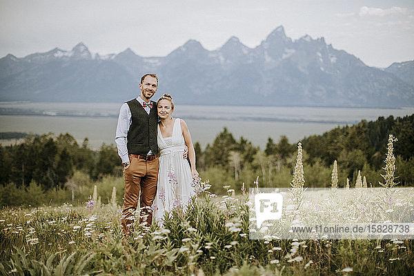 Braut und Bräutigam lächeln und umarmen sich im Feld der Wildblumen