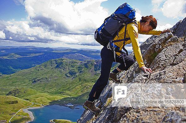 Frau klettert mit Rucksack auf den Snowdonia-Berg
