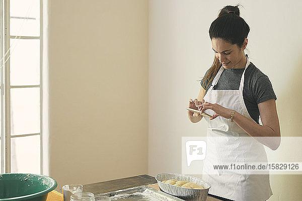 Frau in Schürze fotografiert Challah-Brot mit Smartphone auf dem Tisch an der Wand