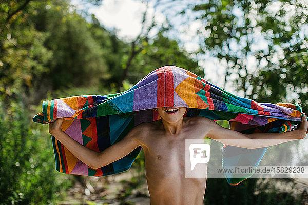 Junge mit Handtuch am Strand in den Sommerferien mit einem großen Lächeln Junge mit Handtuch am Strand in den Sommerferien mit einem großen Lächeln
