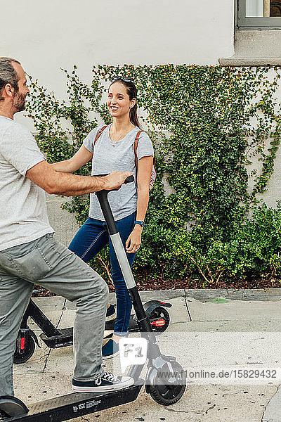 Mann und Frau unterhalten sich auf dem Roller.