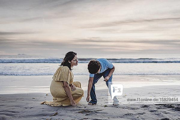 Lebensstil von junger Mutter und schulpflichtigem Sohn auf der Suche nach Muscheln