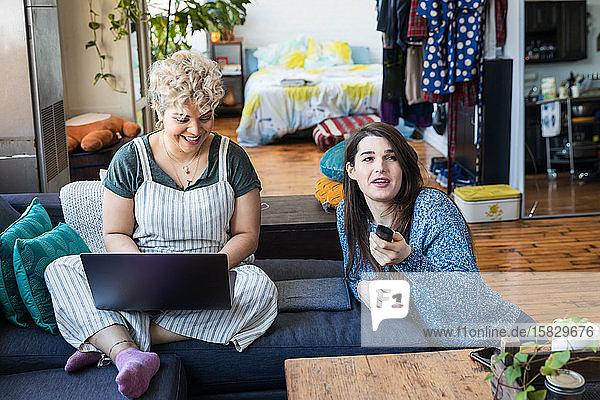 Lächelnde Frau benutzt Laptop  während Mitbewohner zu Hause fernsieht