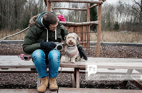 Mann saß mit seinem Hund auf einer Parkbank draußen