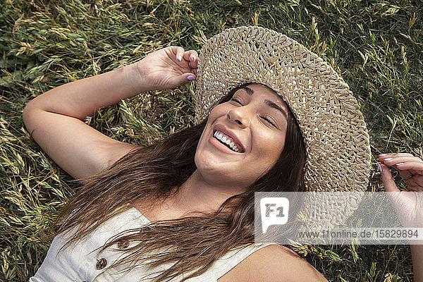 Hübsche Latina-Frau lacht im Gras