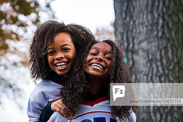 Portrait of cheerful sisters in sports clothing at park