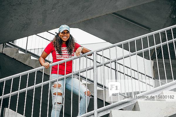 Kreatives Porträt einer lächelnden schwarzen Frau auf einer Treppe