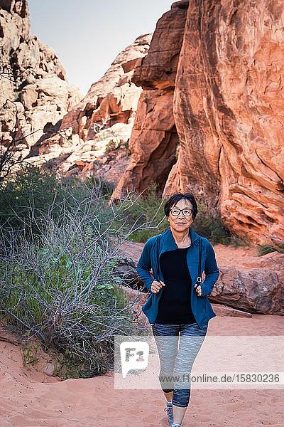 Porträt einer älteren asiatischen Frau  die in der Wüstenlandschaft wandert