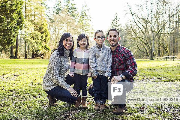 glückliche Eltern posieren mit ihrem Sohn und ihrer Tochter für ein Foto.