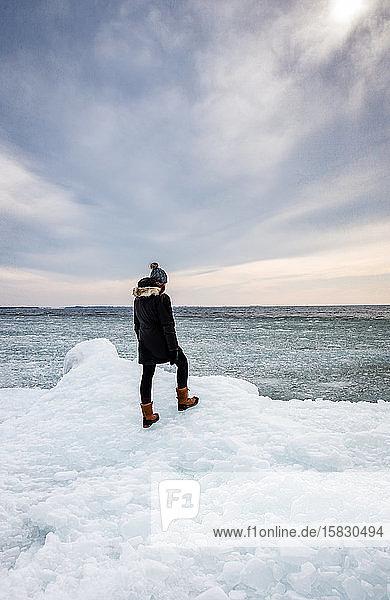 Frau steht am eisigen Ufer eines Sees und schaut in die Ferne.