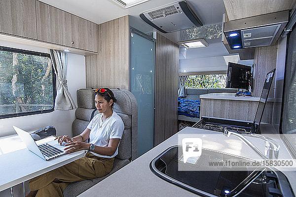 Frau arbeitet an ihrem Laptop in einem Wohnmobil in Australien