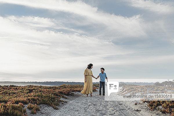 Weitwinkel von Mutter und Sohn beim Strandspaziergang vor wolkenblauem Himmel