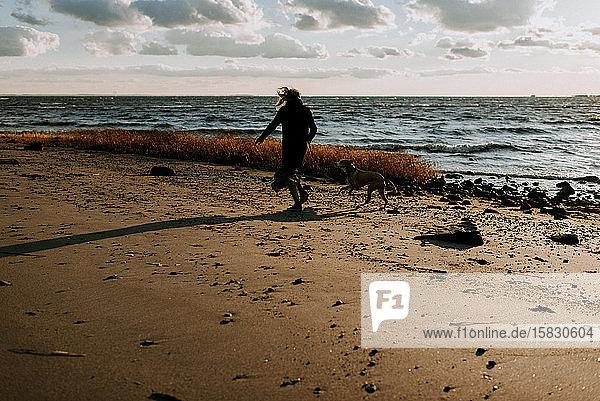 Frau rennt mit Hund am Strand