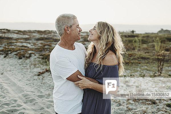 Verheiratetes Paar umarmt sich bei Sonnenuntergang am Strand