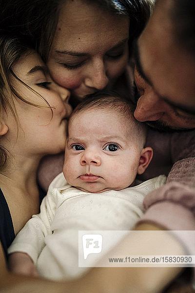 Papa  Mama und große Schwester küssen Neugeborene