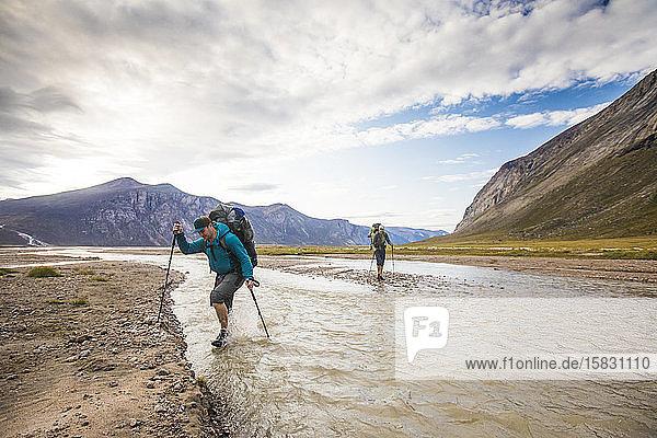 Zwei Rucksacktouristen überqueren den fließenden Fluss während einer Wanderung.