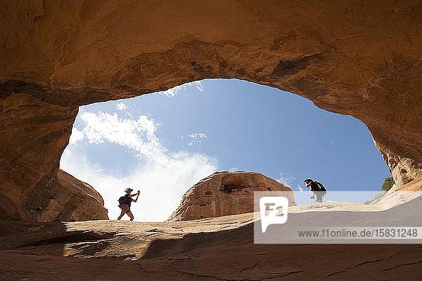 Frauen stehen in einem Felsbogen aus Sandstein  McInnis Canyons  Colorado