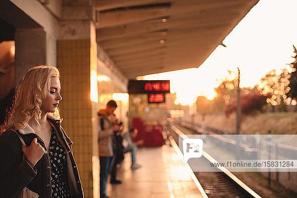 Junge Frau wartet bei Sonnenuntergang am U-Bahnhof auf den Zug