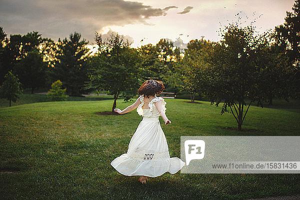 Eine Tänzerin in langem weißen Kleid wirbelt in goldenem Licht im Park bei Sonnenuntergang
