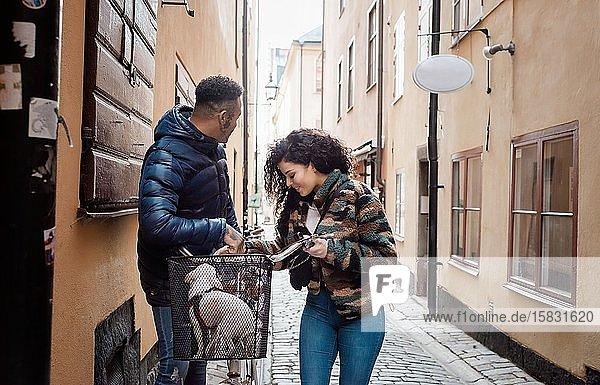 Paar  das zusammen mit seinem Hund im Korb in Europa Fahrrad fährt