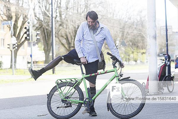 älterer Mann mit Beinprothese wird Fahrrad fahren