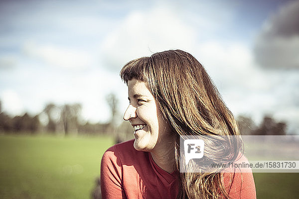 Girl with fringe laughs in sunlight out on green farm land in spring