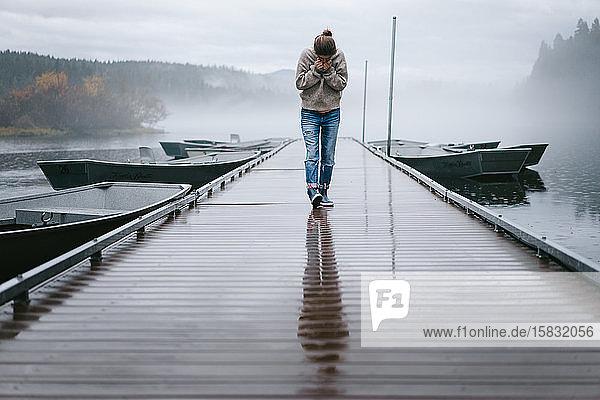Junge Frau schaut nach unten  während sie im Nebel über das nasse Dock läuft
