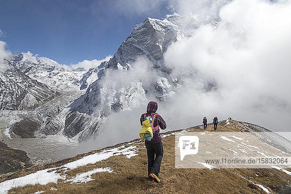 Eine Frau steigt einen sanften Grat in den Nebel hinab  Himalaya-Gipfel im Rücken