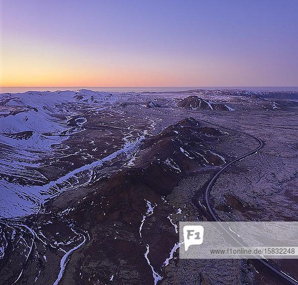 Straße durch verschneites  bergiges Gelände