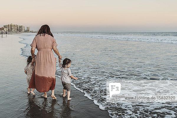 Hinteransicht einer Mutter  die junge Töchter im Meer am Strand spazieren führt