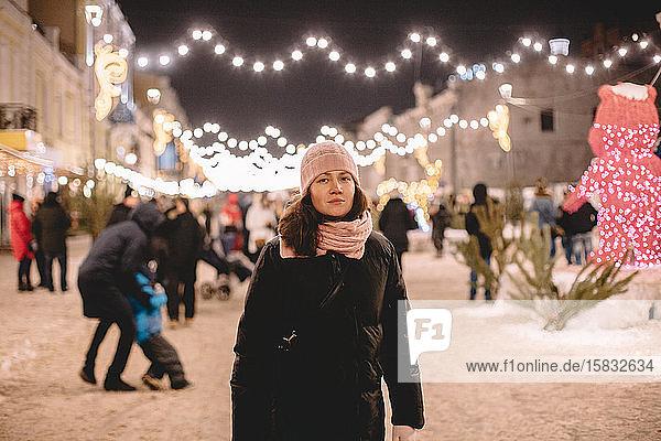 Junge Frau in warmer Kleidung steht in hell erleuchteter Straße
