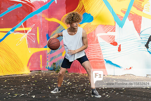 Junge Männer mit kurvenreichem Haar spielen Basketball draußen auf einem Platz