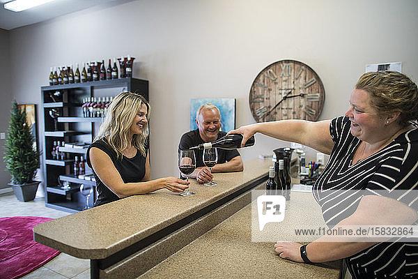 Winzer schenkt ein Glas Rotwein während einer Weinprobe auf einer Weintour ein.