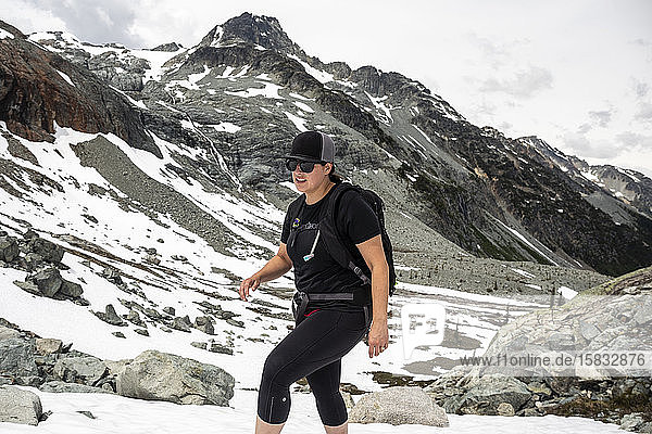 A women hikes up a snow field on a summer day in the mountains for British Columbia.