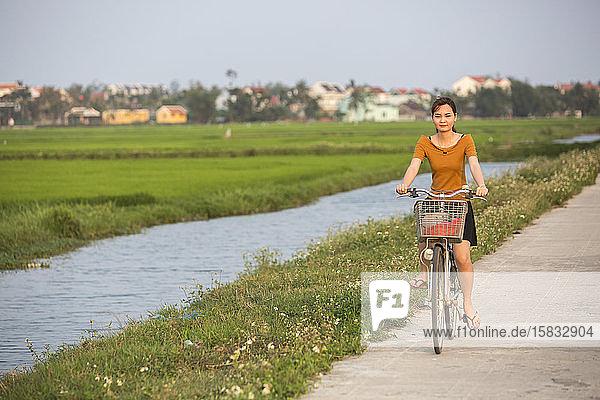 Eine junge Frau fährt mit dem Fahrrad an einem Reisfeld in Hoi An  Vietnam  vorbei.