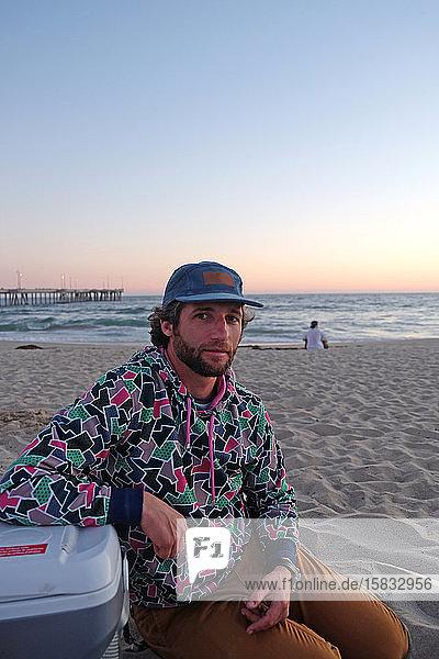 Mann mit Mütze  Bart und lockigem Haar sitzt am Strand bei Sonnenuntergang