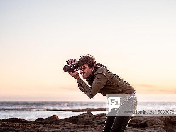 Mann hockt und fotografiert mit Digitalkamera an der Küste