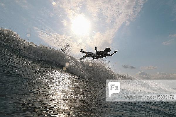 Surfer auf einer Welle zur Zeit des Sonnenuntergangs